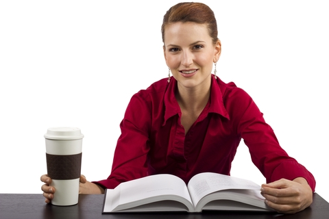 Businesswoman Reading Book and Drinking Coffee
